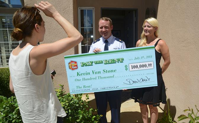 """Maj. Kevin Van Stone, Air Force Operational Test and Evaluation Center Detachment 5, and his wife, Melinda (right), speak to a representative from CBS after being handed a giant check for $100,000 from """"The Price Is Right"""" July 10. Van Stone was part of a military appreciation episode where the audience was entirely made up of military personnel. Van Stone won the prize for winning at the show's """"Pay the Rent"""" game. The episode aired July 4. (U.S. Air Force photo by Kenji Thuloweit)"""