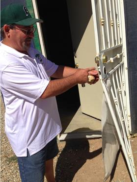 Palmdale Pony Youth Baseball President Russ Monette shows where vandals broke open a door to gain entry to the Pinto Field's score box in the league's far field. (Photo by Jim E. Winburn)