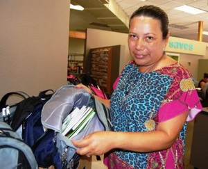 SAVES Coordinator Patricia Morales shows the school supplies inside the backpacks for high school students -- pencil boxes, calculators, erasable pens, dictionaries, three ring binders, notebook paper, erasers, staplers, graph paper, and flash drives.