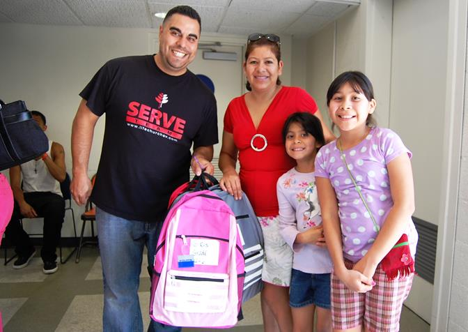 Pastor Abner Diaz of Life Church Antelope Valley (left) gives four backpacks filled with school supplies to Yuliana Garcia and two of her five children. Life Church Antelope Valley donated more than 300 of the 600 backpacks that were distributed to families in need Friday at South Antelope Valley Emergency Services (SAVES).