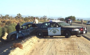 The patrol car hit the CHP officer and threw him into a wash, officials said.