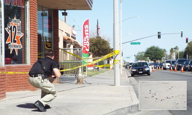 A Sheriff's investigator takes a photograph of the trail of blood that dotted the sidewalk along Palmdale Boulevard following a daylight stabbing Tuesday afternoon. (Photo by LUIS MEZA)