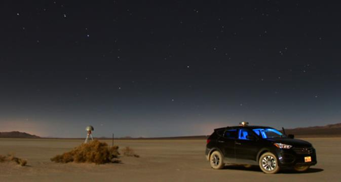 The constellation Ursa Major looms over a GPS-equipped survey vehicle and a ground station to its left at El Mirage Dry Lake. (Credit: NASA /John Sonntag)