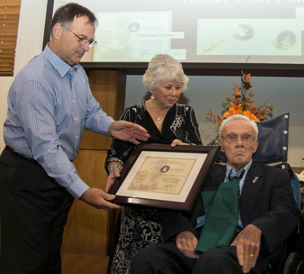 Richard Dilbeck (left), coordinator of the Master Pilot award presentations for the Federal Aviation Administration's Sacramento regional office, presents the award to retired NASA Armstrong research pilot Tom McMurtry as McMurtry's wife Mary Louise assists. (Credit: NASA / Jim Ross)