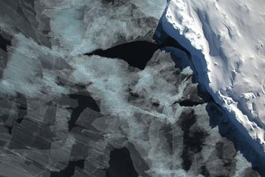 A small hole in the clouds revealed newly formed sea ice in the Bellingshausen Sea next to an iceberg on the Nov. 5, 2014, flight. (NASA / Digital Mapping System)
