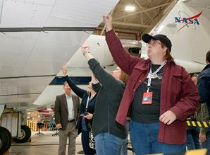 Project Manager Tom Rigney gives Valerie Skuovaty, Melissa Aho and Trina Marie Phillips a hands-on look at the ACTE flap on NASA's Gulfstream III aircraft. (NASA / Tom Tschida)