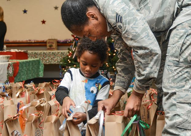 Senior Airman Chasaneya Jones, 412th Operations Support Squadron fills bags of cookies with the help of her son, Airess. (U.S. Air Force photo by Rebecca Amber)