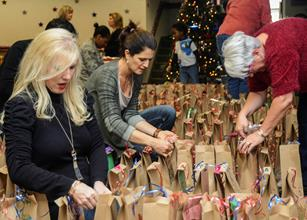 (L to R) Denise Smith, Kimberly Leshinsky and Sue Kovras pack dozens of cookies into brown paper bags during the annual Airman's Holiday Cookie Drive at the Airman and Family Readiness Center Dec. 3. (U.S. Air Force photo by Rebecca Amber)
