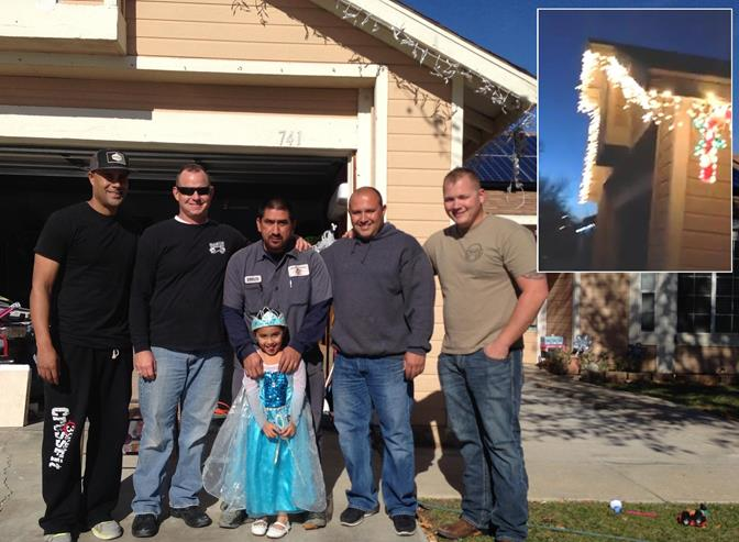 Four-year-old brain cancer patient Emily and her dad, Emilio, pose for a picture with the kindhearted local deputies who set up the family's Christmas lights Thursday, Dec. 19. [Contributed]