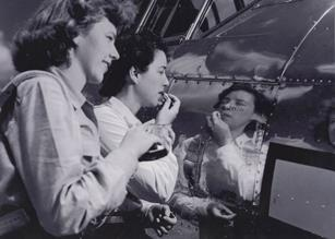 W.A.S.P.s Flora Belle (Smith) Reece and Dorothy Allen put on make up in the reflection of a P-38.  (U.S. Air Force photo)