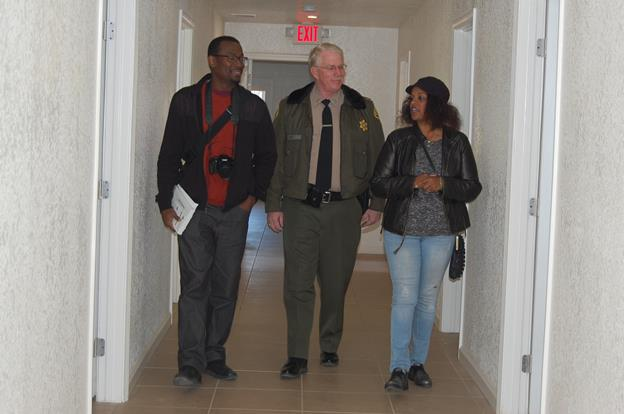 "[L to R]  AV YouthBuild Mentor Coordinator Jamaal Brown, Palmdale Sheriff's Station Caption Don Ford and AV Pageantry Director Waunette Cullors tour the co-ed wing of the Palmdale Dream Center. Cullors is ""adopting"" two rooms at the new facility. ""It's important for AV Pageantry to support this project because we're supporting girls, and I think this is a very good program to get them back on their feet,"" Cullors said. ""We want them to know that they're loved, they're part of the community, and they should have the best of things."""