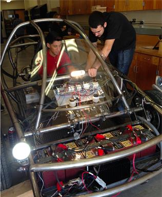 Kyle Barrett (right) explains various features of the electric car project to Erick Fuentes. (JIM E. WINBURN)