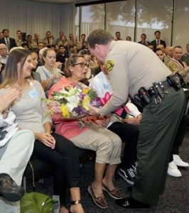 Sheriff Jim McDonnell presents flowers to shooting victim Teresa Van Dongen at the Lifesaving Awards ceremony Wednesday. (LASD)