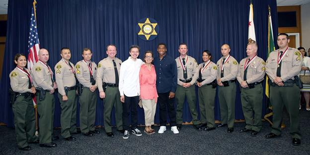 The nine honorees from the Palmdale Sheriff's Station are pictured with the woman they helped rescue, Teresa Van Dongen,  and her sons, John Austin Van Dongen and Dameon Baber (center), along with Sheriff Jim McDonnell. (Photo courtesy LASD)