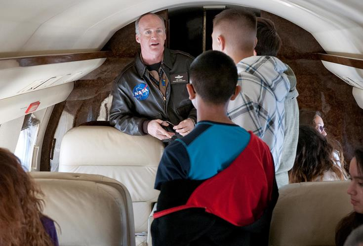 Pilot Troy Asher chats with students inside the G-II aircraft.