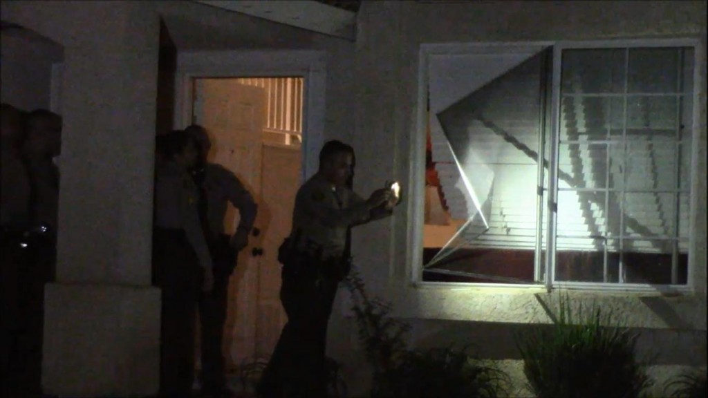 Responding deputies look at a wrecked window screen at the home early Wednesday morning. (Photo by LUIS MEZA)