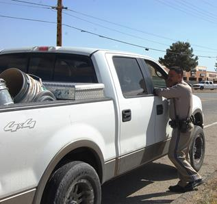 A motorist is stopped Tuesday after he was spotted driving slowly on a dirt road with a cellphone held up to his ear.