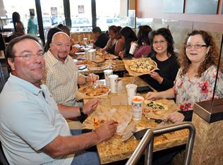 Residents enjoy pizza at a pre-opening party Tuesday, March 31.