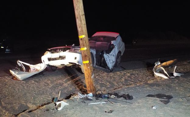The collision left the Honda Civic wrapped around the utility pole in an upright position, according to witnesses at the scene. The Los Angeles County Fire Department removed the car from the pole and extricated its driver, witnesses said. (Photo by LUIS MEZA)