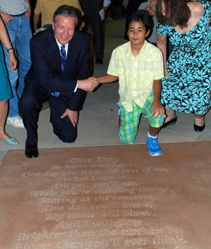 """Palmdale Mayor Jim Ledford congratulates 2014 Walk on Words Poetry Contest winner Steven Brito, whose poem """"One Day"""" was stamped in concrete at the Palmdale Playhouse. [Read more about that here.]"""
