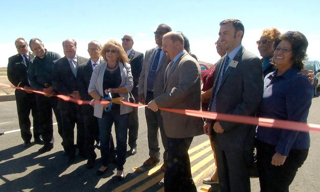 Dory Peterson of the Anaverde Homeowner's Association cuts the ribbon for  the official opening of the Avenue S to Elizabeth Lake connector road. ( City of Palmdale.]
