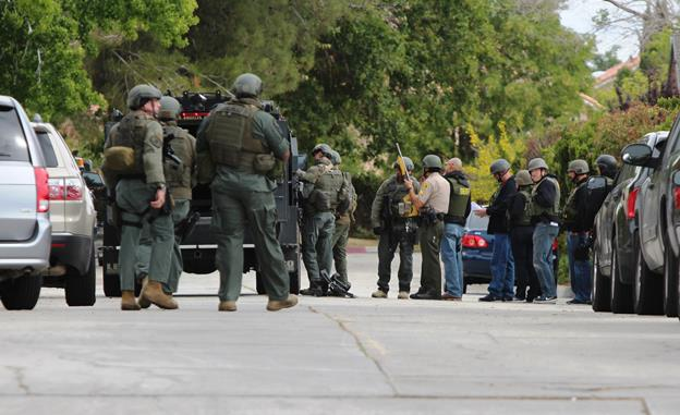 Officers gather near the 43600 block of Park Avenue in Lancaster Friday, May 15. A Los Angeles County sheriff's Special Weapons Team was called in to assist in arresting Rodrick Brumfield, a 29-year-old Los Angeles area resident wanted on a $1-million warrant of a home invasion robbery in the city of Camarillo. (Photo by TONY CHEVAL)