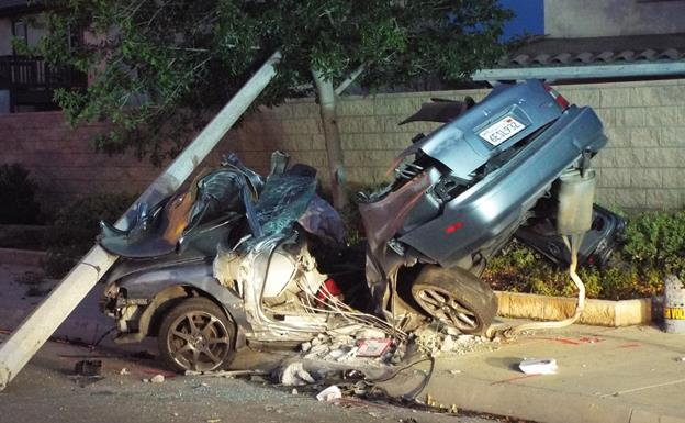 The pole was knocked over and live wires prevented Los Angeles County firefighters from removing the man from his car until Southern California Edison workers arrived to cut power to the wires and take the pole off the car, officials said. (Photo by LUIS MEZA)