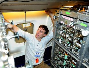 Matthew Irish, a senior Climate Impact Engineering major at the University of Michigan, attaches tubing to the Whole Air Sampler (WAS) instrument installed on the NASA DC-8 airborne laboratory. (contributed)