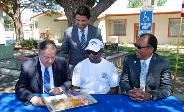 Palmdale Mayor Jim Ledford, left, gets ready to taste a sample of the lunches that will be provided free to kids 18 and under. Looking on, seated left to right, Pastor Darrell Downs and Councilmember Fred Thompson. Standing is Palmdale School District Superintendent Raul Maldonado. (contributed photo)