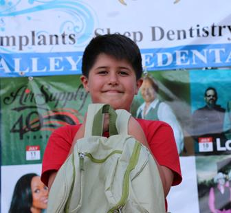"""Jordan Hernandez of Lancaster was caught """"green handed"""" last week at TNOTS and was presented with a backpack courtesy of Waste Management made of recycled materials full of treats, including day passes to DryTown."""