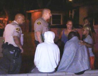 Some of home's occupants speak with local deputies at the scene. (LUIS MEZA)