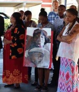 Family members of Michael Davis, including his Mother, Yolanda (right), display a portrait of the victim at a July 3 community press conference. (photo by Jim E. Winburn)