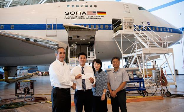 NASA's Armstrong Flight Research Center Director David McBride, left, presents a scholarship check to Ted Kim in front of the Stratospheric Observatory for Infrared Astronomy. Hyan Dae and Eun Joo Kim, Kim's parents, also are pictured. [NASA photo by Carla Thomas]
