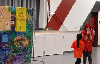 A young volunteer helps Sparky the Wonderbuy defeat the evil Dragonfly after taking the electrical safety bug's oath of loyalty and becoming an honorary member of the Bug Brigade in order to hypnotize the Dragonfly. [Cathy Hart/Southern California Edison]