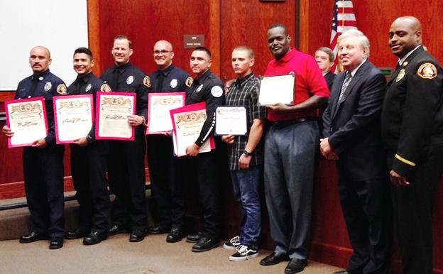 The Palmdale City Council at its Wednesday meeting recognized emergency responders who saved the life of retired L.A. City Fire Capt. David Moore. Pictured from the left: Fire Station 24 Captain Paul Stump, Engineer John Miller, Firefighter Andy Morales, Firefighter Paramedic Robert Metro, Firefighter Paramedic Brad Wolfenstein, and American Medical Response EMT Patrick Perez, retired Fire Capt. Moore, Mayor Pro Tem Mike Dispenza, and L.A. County Fire Division V Assistant Fire Chief Gerald Cosey. (Photo by Jim Winburn)