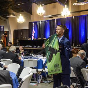 Airman 1st Class Cory Bond, 412th Communications Squadron, shows a poster of the SR-71 during the live auction at the annual Gathering of Eagles. (Rebecca Amber)