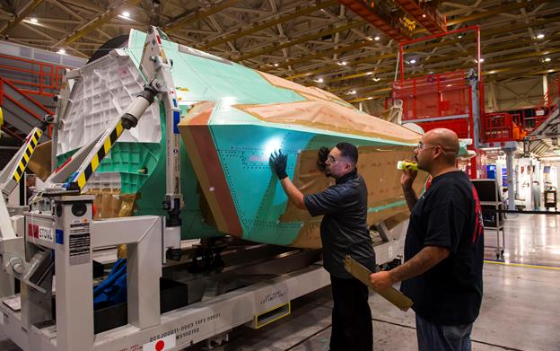Mechanics from Northrop Grumman's F-35 program team in Palmdale, Calif. check the quality of workmanship that went into producing AX-5, the center fuselage that will become a central part of the first F-35 Joint Strike Fighter assembled by Japan. [contributed]