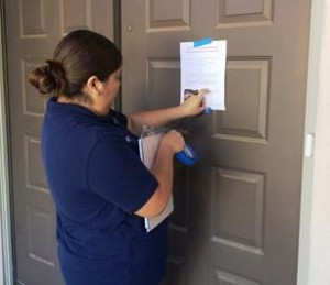 Office Assistant Kayla Macias leaves a flyer on the door of a home. [contributed]