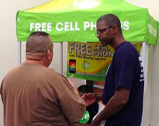 Jonathan Slack, business owner of Free Phones 4 U, discusses free government lifeline cell phones with a customer at Antelope Valley Re-entry Coalition's one-stop community resource fair on Wednesday. (Photo by Jim Winburn)