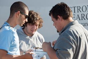 NASA's Hussein Nasr, Orlando Mielke and Bogdan Pugach perform final checks on the Prandtl-m flight computer before a flight. [NASA Photo / Lauren Hughes]