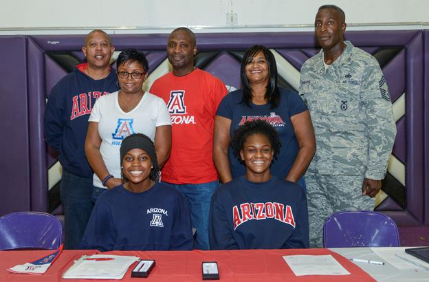 On Nov. 13, Devyn Cross (seated left) and Elizabeth Shelton signed National Letters of Intent to attend the University of Arizona next fall on volleyball scholarships. The students were joined by their parents (left to right) James Culver, Lisa Cross-Culver, James Culver; and LaConger Shelton and Chief Master Sgt. Darrell Shelton. (U.S. Air Force photo by Rebecca Amber)