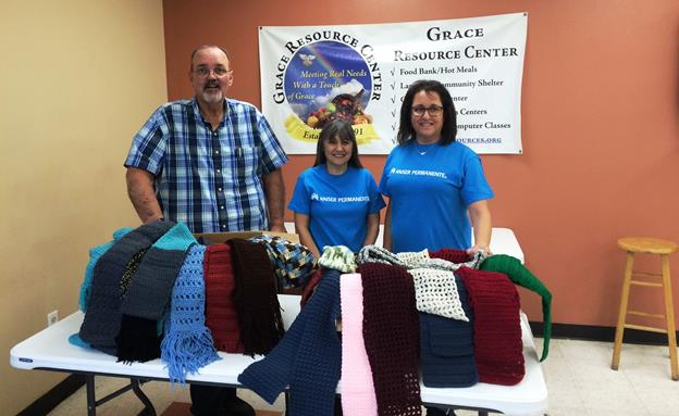 (L to R): Steve Baker from Grace Resource Center accepts a donation of more than 140 hand-crocheted scarves from Sandy Peterson and Liz Spinella-Jones. [contributed]