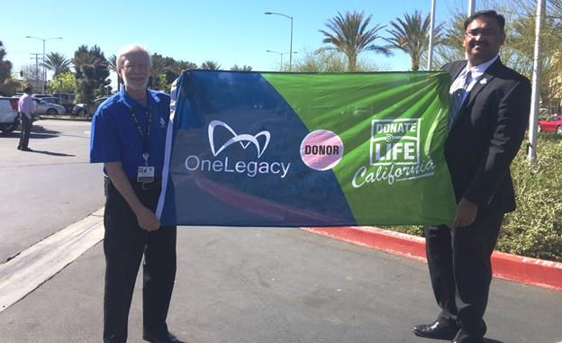John Rossfeld, chief executive officer of Antelope Valley Hospital, (left) and Prasad Garimella, chief operating officer of OneLegacy, hold the Donate Life flag. The flag will fly at the main entrance of the hospital throughout April to commemorate National Donate Life Month. [contributed]