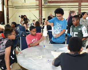 Students from Discovery School in Lancaster broke into teams to build a rocket out of a soda bottle, manila folders and tape during the hands-on portion of their tour to the Air Force Research Laboratory's Propulsion Directorate here at Edwards AFB April 19. The students then got to launch their rockets. (U.S. Air Force photo by Kenji Thuloweit)