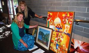 """Jennifer Tallakson (kneeling) and Debbie Barrientes prepare to hang pieces of art at the Palmdale Playhouse for the 2015 """"The Generations"""" exhibit. [contributed]"""