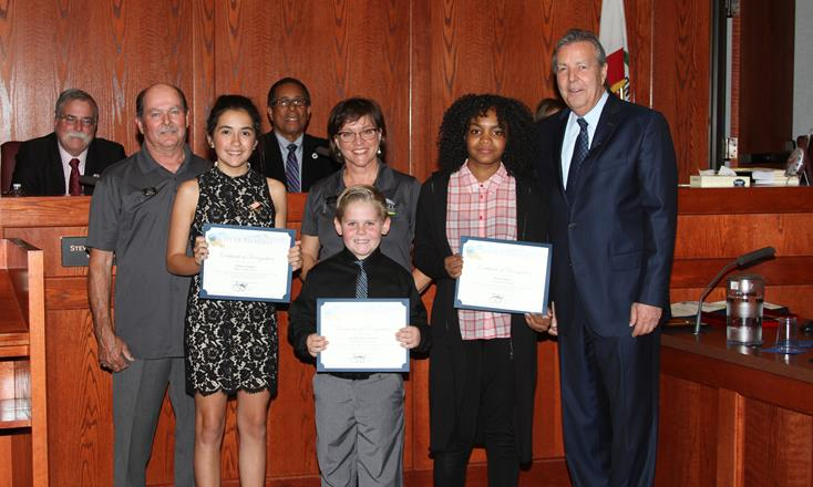 The winners were announced at the Nov. 2 Palmdale City Council Meeting. [ Seated in back (L to R): Mayor Pro Tem Steve Hofbauer and Councilmember Fred Thompson. Standing (L to R): Mike Bertell, contest winner Lillian Collado, Stacia Nemeth, contest winner Persja Moore, Mayor Jim Ledford. Standing, front row: Contest winner Nicholas Howlett. [Contributed photo]